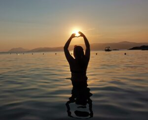 Images of girl in the sunset doing a heart sign with her hands