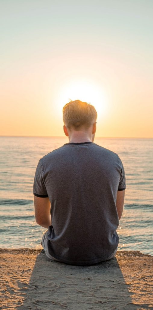 Image of tranquil man sitting on the beach looking at the sea